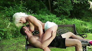 Tow-haired cougar uses a pole nearly a park to ride a big dick