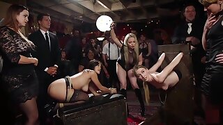 The House once again finds itself packed wall to wall with beautiful kinky swingers, but this time instead of a senior submissive to train the new meat, we have two pieces of untrained, but enthusiastic ass. Interviewed about their skills and how they plan to get their training, one claims to be a blond electro slut with a wet mouth for fucking, and the other an out and out anal whore, willing to give up all her holes for the chance to train and learn The Upper Floor Rules. Lucky for both girls, previous servants of the house are in attendance, and unfortunately for them they only want to humiliate the girls and make them lick their high heels. It becomes clear after some goveling and oral shoe shining, the new girls will have to battle for the right to the training collar with a show of submissive fucking, bondage, and a sadistic gauntlet in their areas of speciality. The first scene finds Kendra Spade with her big round ass tied up in the air, her cunt clipped shut, and her submissive sister in the hardwood stocks. Riley Reyes has claimed to be a real servant of electrical torment, so Aiden Starr threw her right into the stocks, stuffed a huge electro plug in her cunt and tied it there for good measure. As Ramon sets in on Kendra's gorgeous ass, gaping her hole and denying her pleads to cum, Aiden slowly stalks Riley, turning the electro plug up more and more and Stefanos stuffs a hitachi against her trapped clit, causing her to squirt all over herself and scream around the hard cock in her mouth. Riley's gorgeous pale nipples are clamped heavily, but not as heavily as Kendra is getting her ass pounded out. The crowd of horny swingers urge them to with cheers, and head off into the darkness to make their own mischief. Partner swapping, blow bangs, tight rope suspensions, floggings, spankings, and fucking on the floor is just some of the extra action du jour. Aiden Starr finds Riley amidst all the sexual madness and promises her the collar if she will just perform Aiden a few small favors. One of those not so small favors is Aiden's fist in Riley's pretty pink pussy, which she presents willingly to Aiden. Aiden teaches her to beg and what to scream when she cumming uncontrollably. She is made to shock herself on command, take a beating on her milky white tits, and finally lick her mistresses perfect pussy until she cums all over Riley's face. Alas, Riley is tricked into disobeying a small rule, denying her the collar and leaving her to pout with the Governess' taste still on her lips. Bella Rossi has come back as a guest for the night and brought her handsome date Dozer, who is quick to lay Bella down and flog, spank, and command her to shake her beautiful ass. Next order of business it those celestial tits we all worship, being used for a long and submissive titty fucking. Bella is all worked up, and gags and drools on Dozer's cock until she given permission to slip his hard cock into her wet pussy, working him with all of her moves until her rewards her with a hot load all over her pretty face and glistening tits. Welcome back Ms. Rossi,